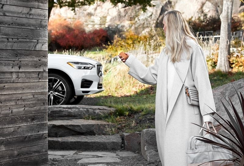A woman holding a cellphone looking at a Volvo